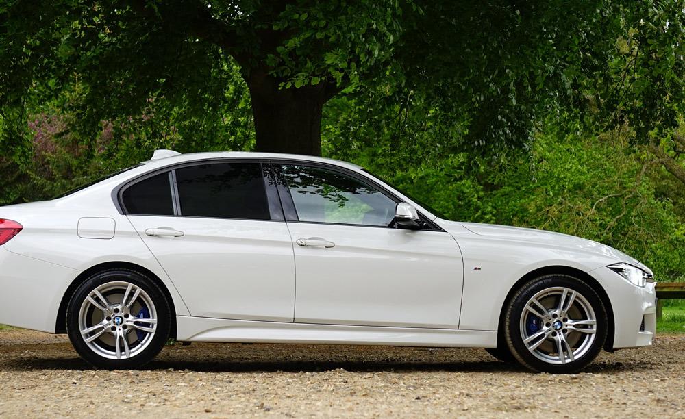 Ein weißer BMW im Park mit getönten Schieben