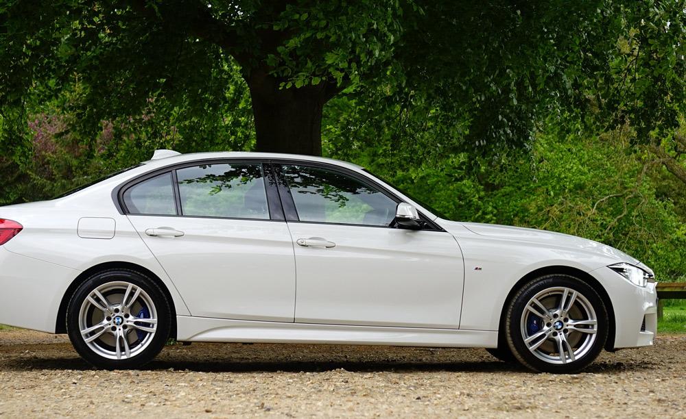 Ein weißer BMW im Park mit ungetönten Schieben