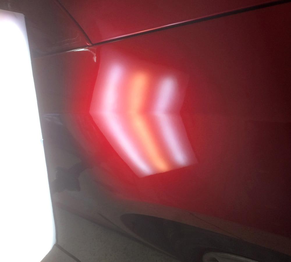 Nahaufnahme eines Autos nach einer Dellenentfernung unter dem Licht einer Fixierlampe